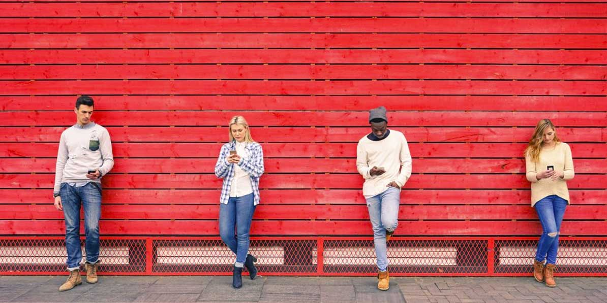 Two men and two women looking at their smartphones with a red backdrop